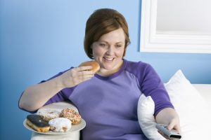 Overweight woman eating Doughnuts