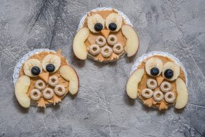 Funny owl with peanut butter and fruits on rice cake