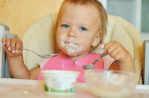 Baby Eating with two spoons