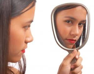 Unhappy woman looking in a mirror