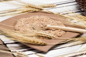 Wooden spoon with wheat bran and wheat ears